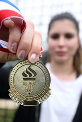 Horace Greeley junior Kira Lindner, 16, holds the first medal she received in throwing at age 10, at the high school April 18, 2019.