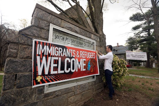 Rev. Drew Paton, rector of South Presbyterian Church, adjusts a sign welcoming immigrants and refugees outside the church in Dobbs Ferry April 19, 2019.  The church is raising money to build an apartment within the church to serve as a sanctuary for immigrant families fighting imminent deportation.