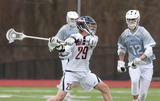 Briarcliff's Matt Waterhouse (29) fires a shot in front of Bronxville's Clark Stephens (12) during boys lacrosse action at Briarcliff High School  April 18,  2019. Bronxville won the game 8-7.