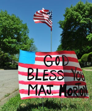 Flags and welcome signs lined the sidewalks and roadway on Milby Avenue Friday afternoon welcoming Major Any Morton home.