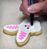 Sam Beauchamp uses a food-safe marker to add fine details to one of her decorated Easter cookies.