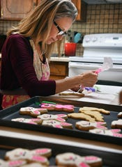 Sam Beauchamp, owner of Cakey Bakey Art, decorates Easter cookies in her home kitchen.