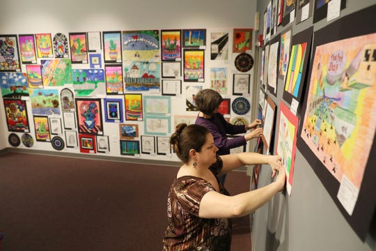 Misty Johnson and Marcia Hartman hang art for the Muskingum County K-12 Student Art Exhibition at the Zanesville Museum of Art.