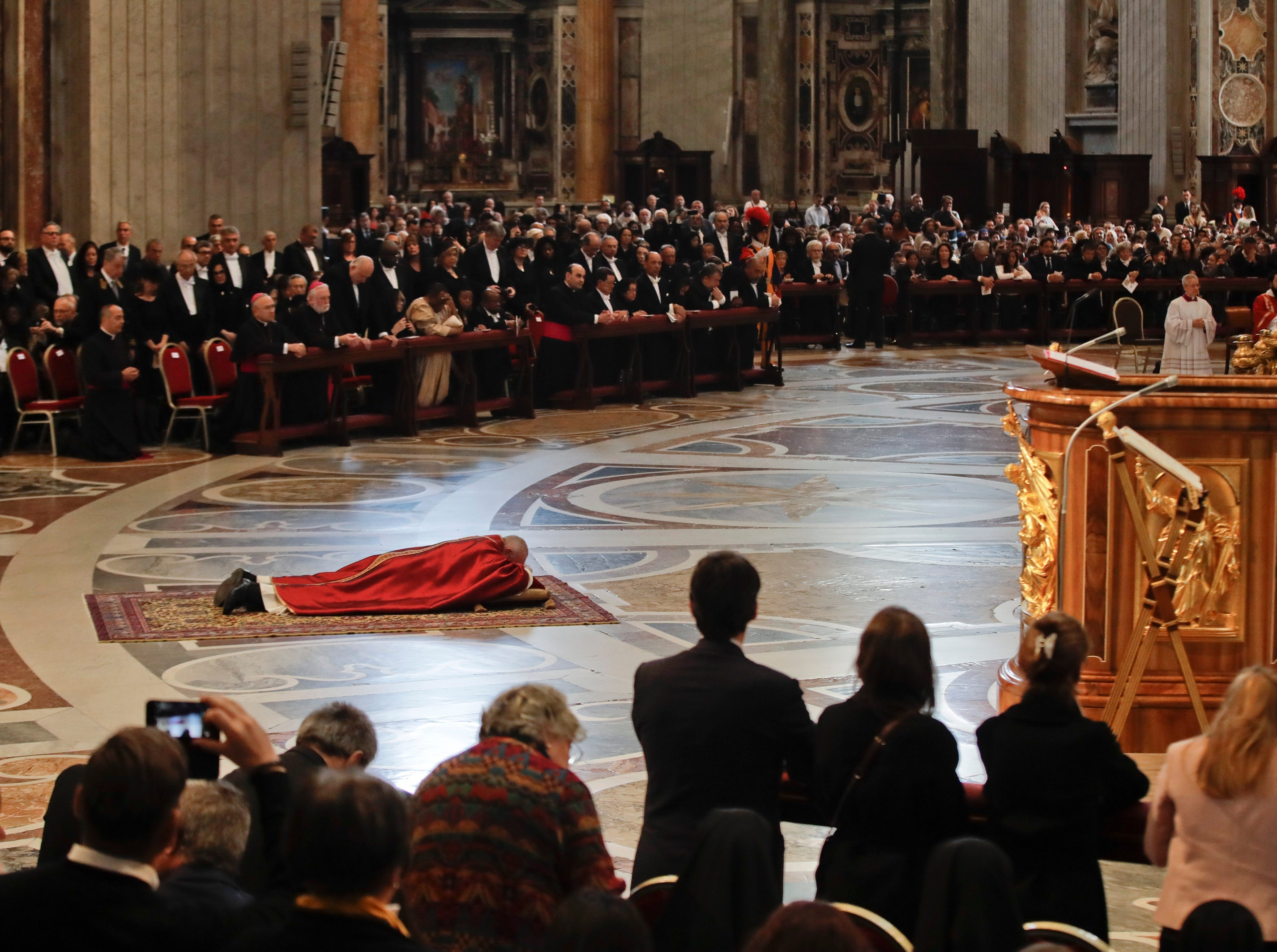Pope Francis lies down in prayer prior to celebrate Mass for the Passion of Christ at St. Peter's Basilica, at the Vatican, Friday, April 19, 2019. Pope Francis began the Good Friday service at the Vatican with the Passion of Christ Mass and hours later will go to the ancient Colosseum in Rome for the traditional Way of the Cross procession.