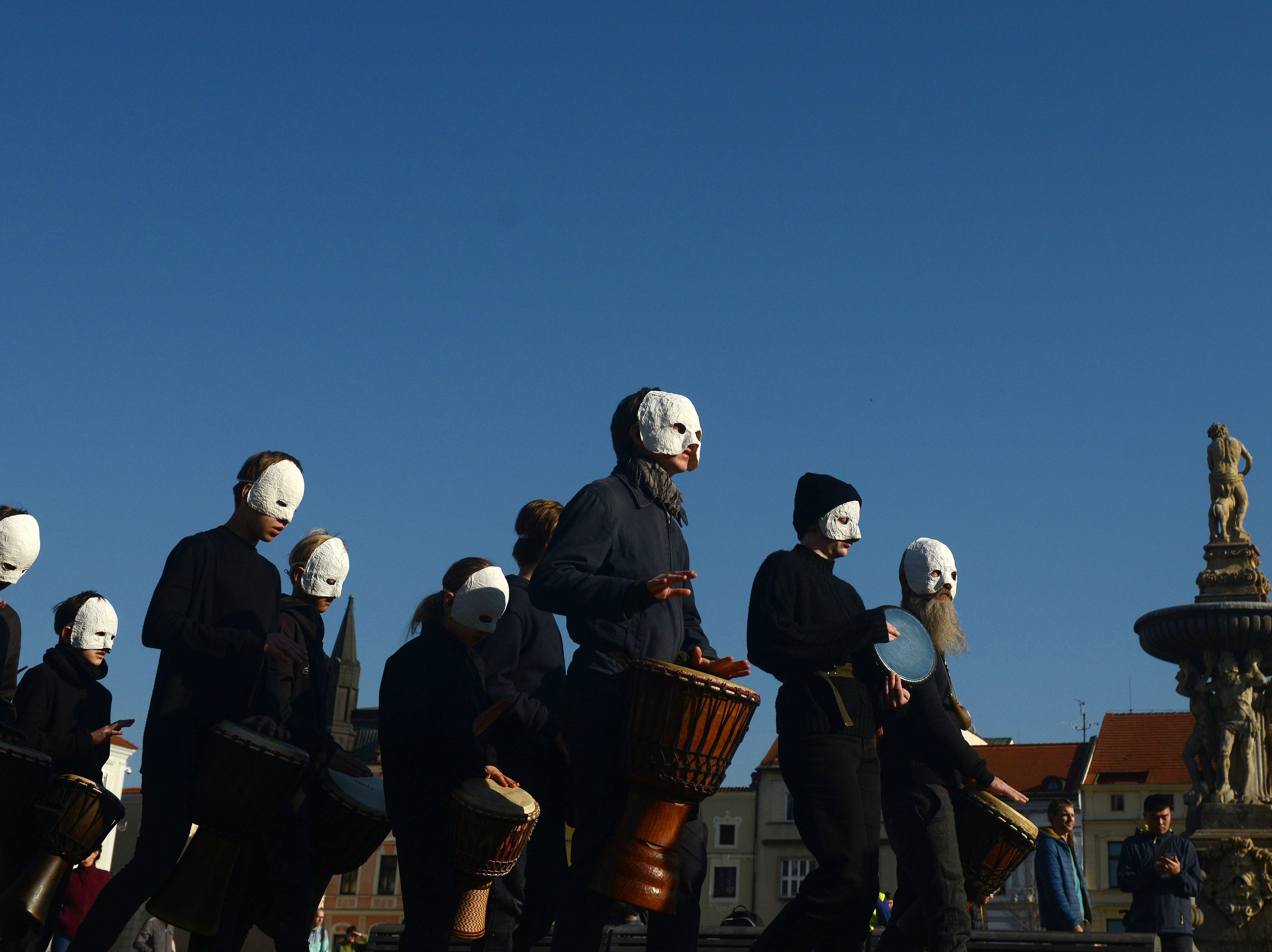 People, wearing white masks, play music during a Czech Easter traditional ritual to mark Good Friday, that recalls for Christians the crucifixion of Jesus Christ ahead of Easter Sunday, on April 19, 2019 in Ceske Budejovice. Christians around the world are marking the Holy Week, commemorating the crucifixion of Jesus Christ, leading up to his resurrection on Easter.