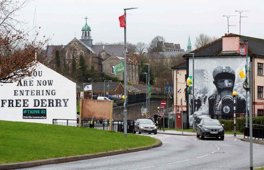 Cars pass murals in Derry, Northern Ireland, on March 13, 2019.