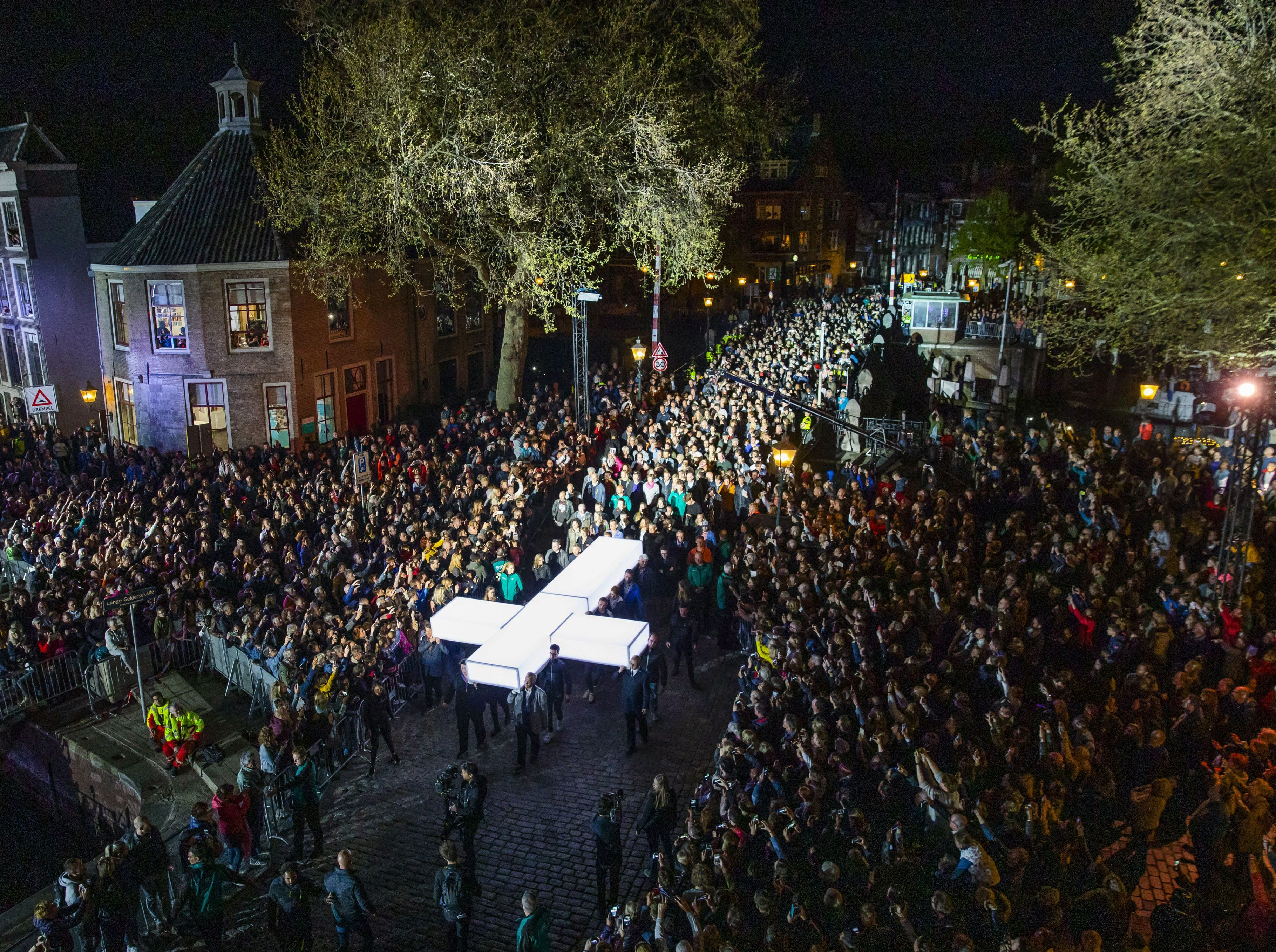 """People carry a white cross during a broadcast procession of """"The Passion"""" by Dutch TV Evangelical Broadcasting through the streets of Dordrecht, on April 18, 2019."""