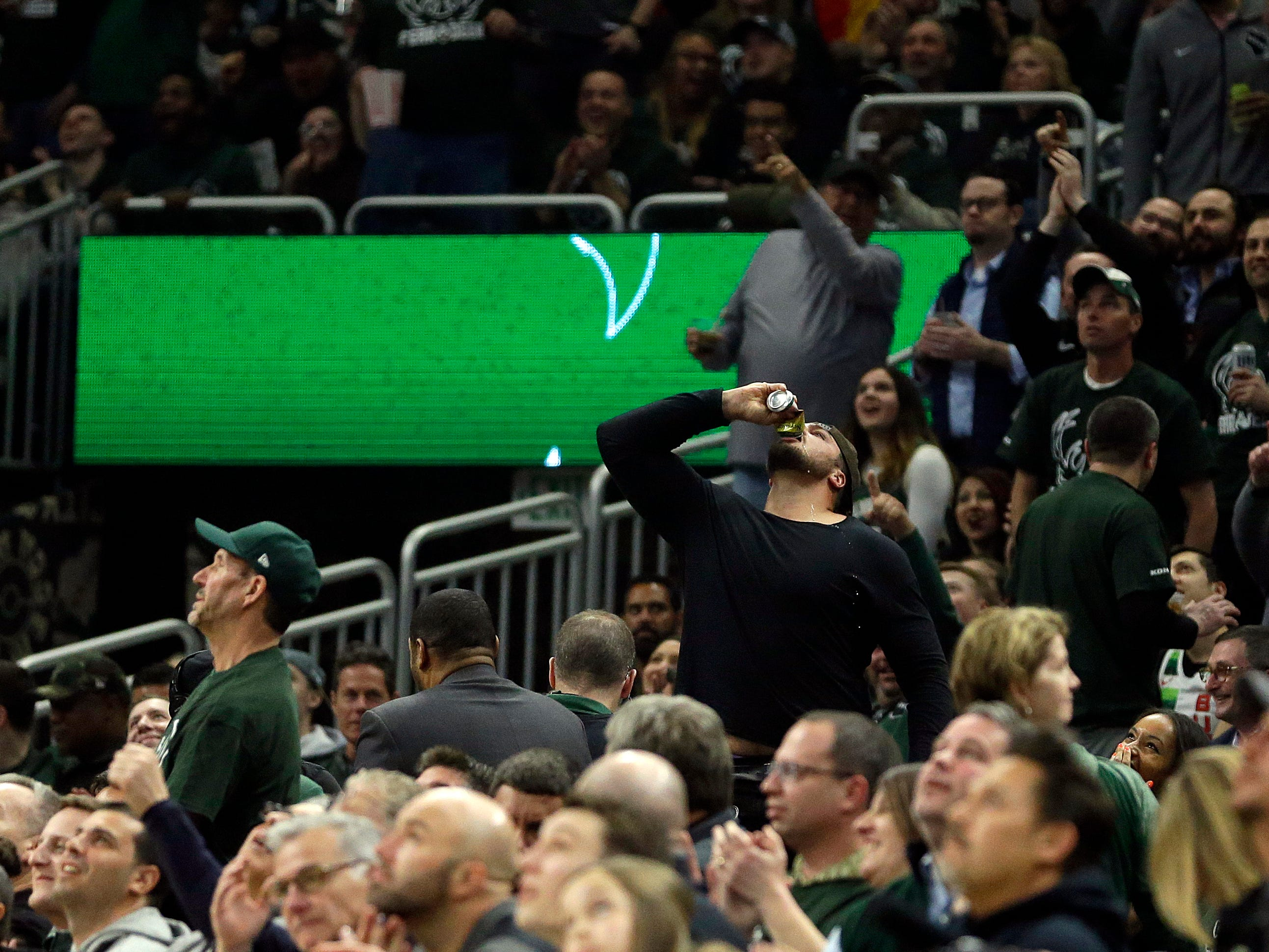 April 17: Packers offensive lineman David Bakhtiari chugs a beer and fires up the crowd during Game 2 between the Bucks and Pistons in Milwaukee.