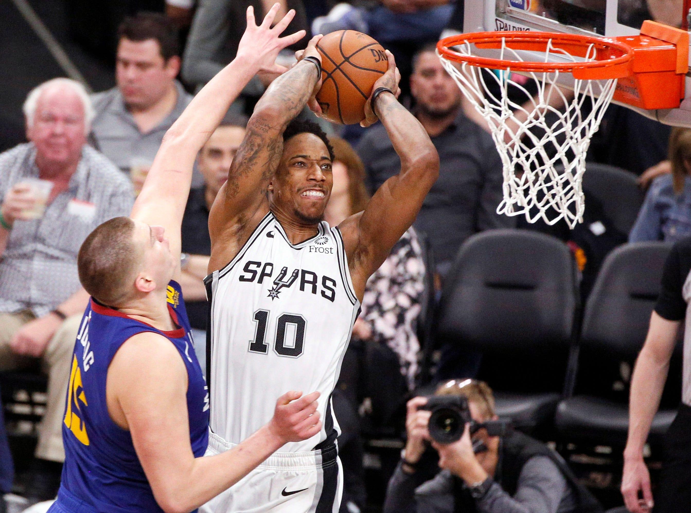 April 18: Spurs guard DeMar DeRozan (10) rises up for the two-handed flush over Nuggets defender Nikola Jokic (15) during Game 4.
