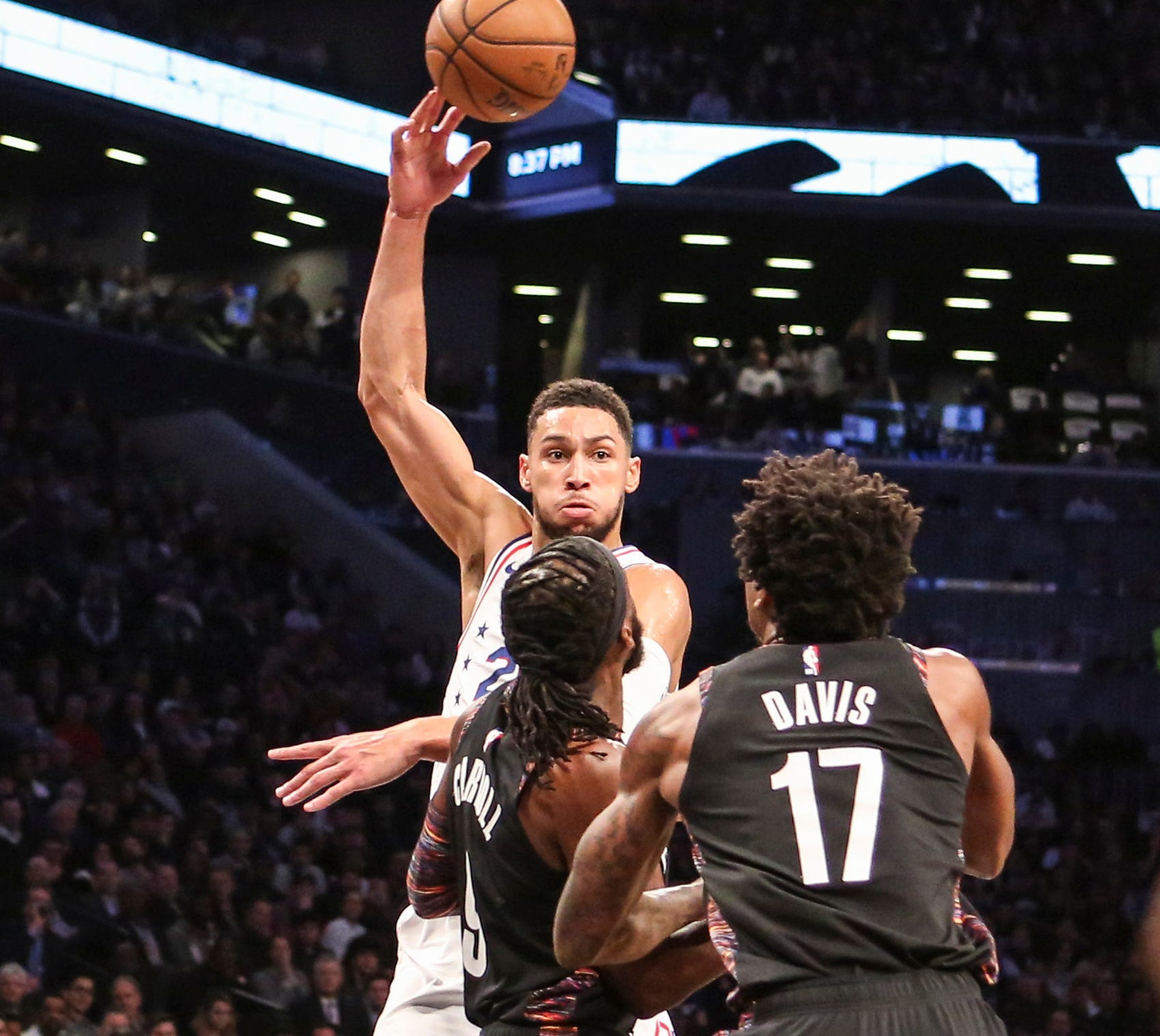 April 18: Sixers forward Ben Simmons (25) pass over Nets defenders DeMarre Carroll (9) and Ed Davis (17) during Game 4 in Brooklyn.