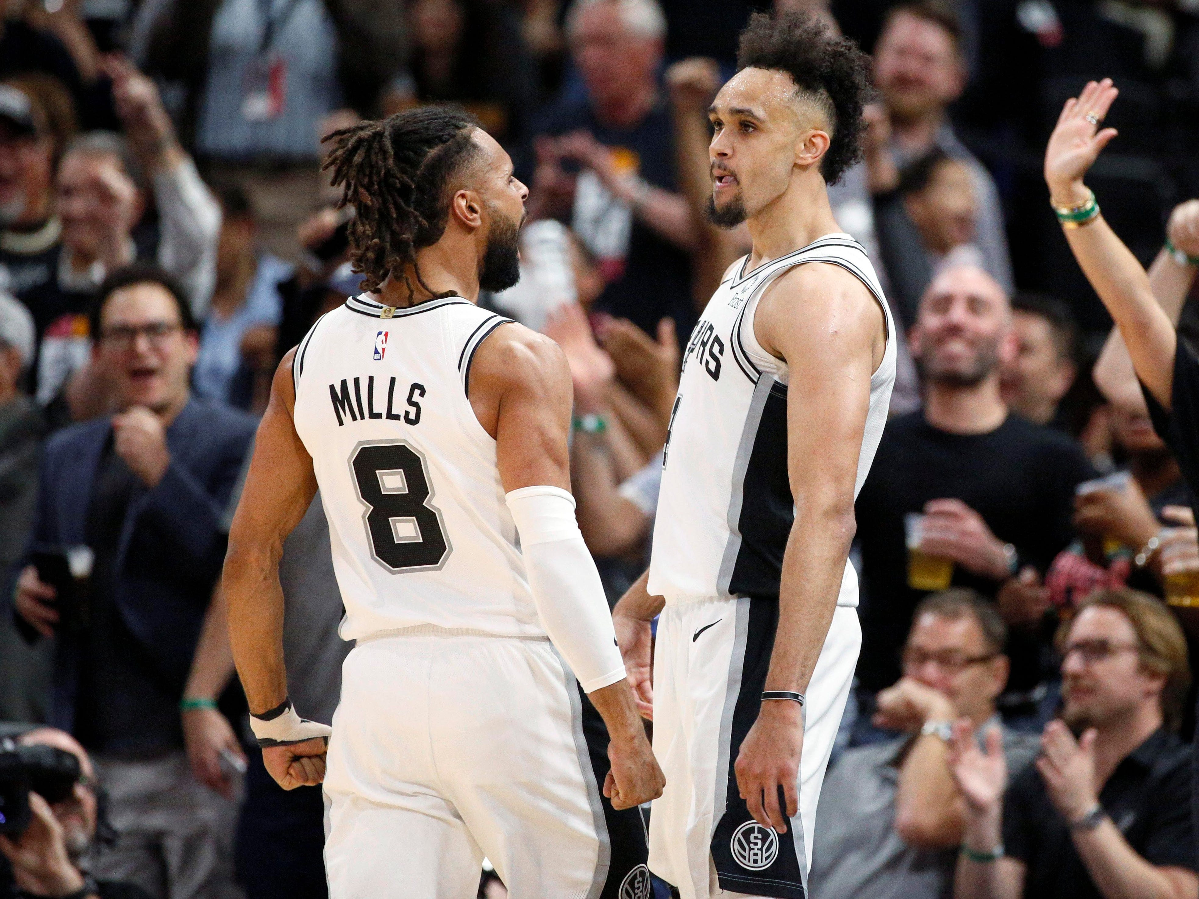 April 18: Spurs guard Derrick White celebrates a big second-half bucket with Patty Mills during Game 3 against the Nuggets.