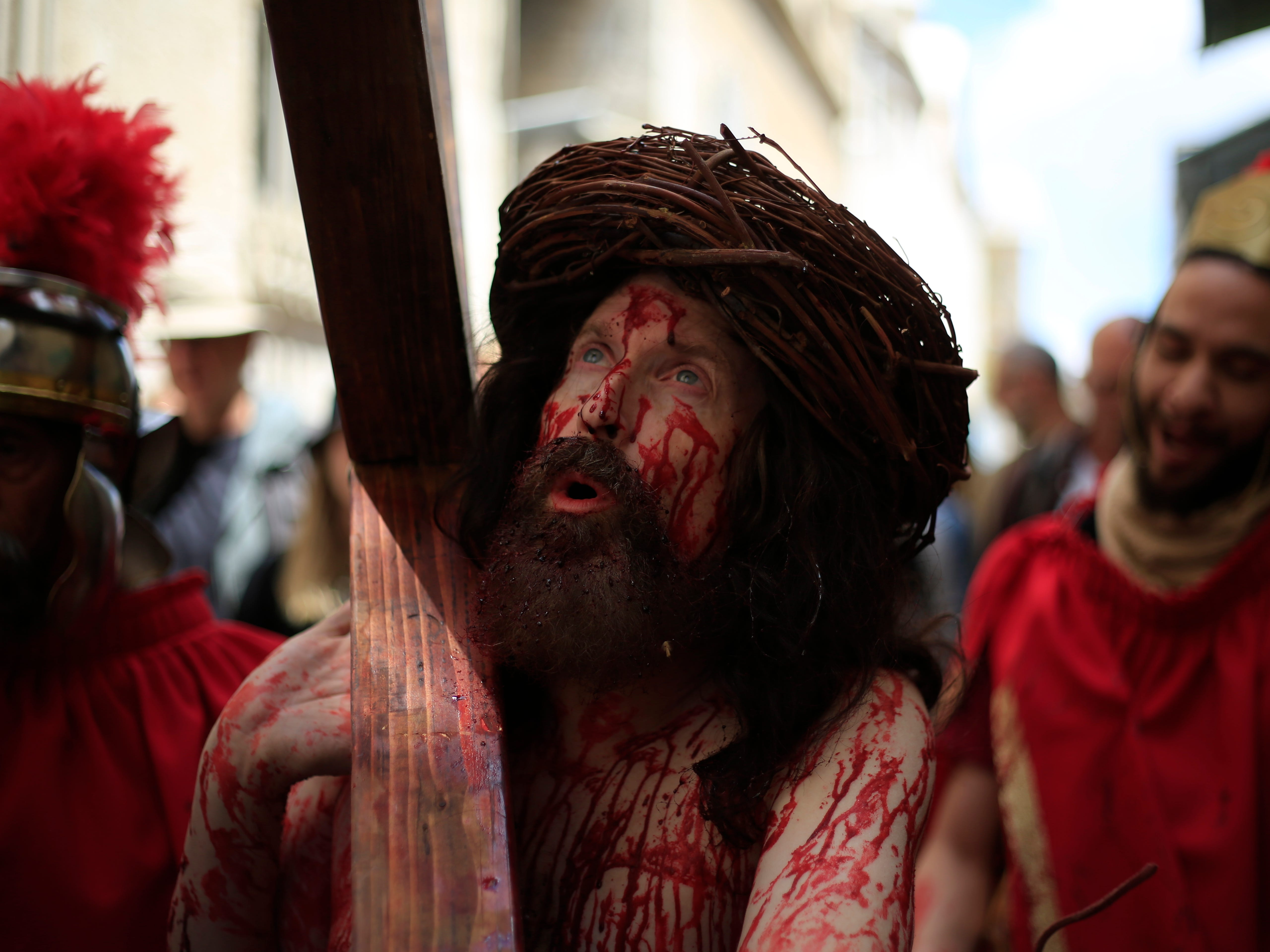 An actor dressed as Jesus Christ carries a cross as he reenacts the crucifixion walk along the Via Dolorosa towards the Church of the Holy Sepulchre, traditionally believed by many to be the site of the crucifixion of Jesus Christ, during the Good Friday procession in Jerusalem's old city, Friday, April 19, 2019.