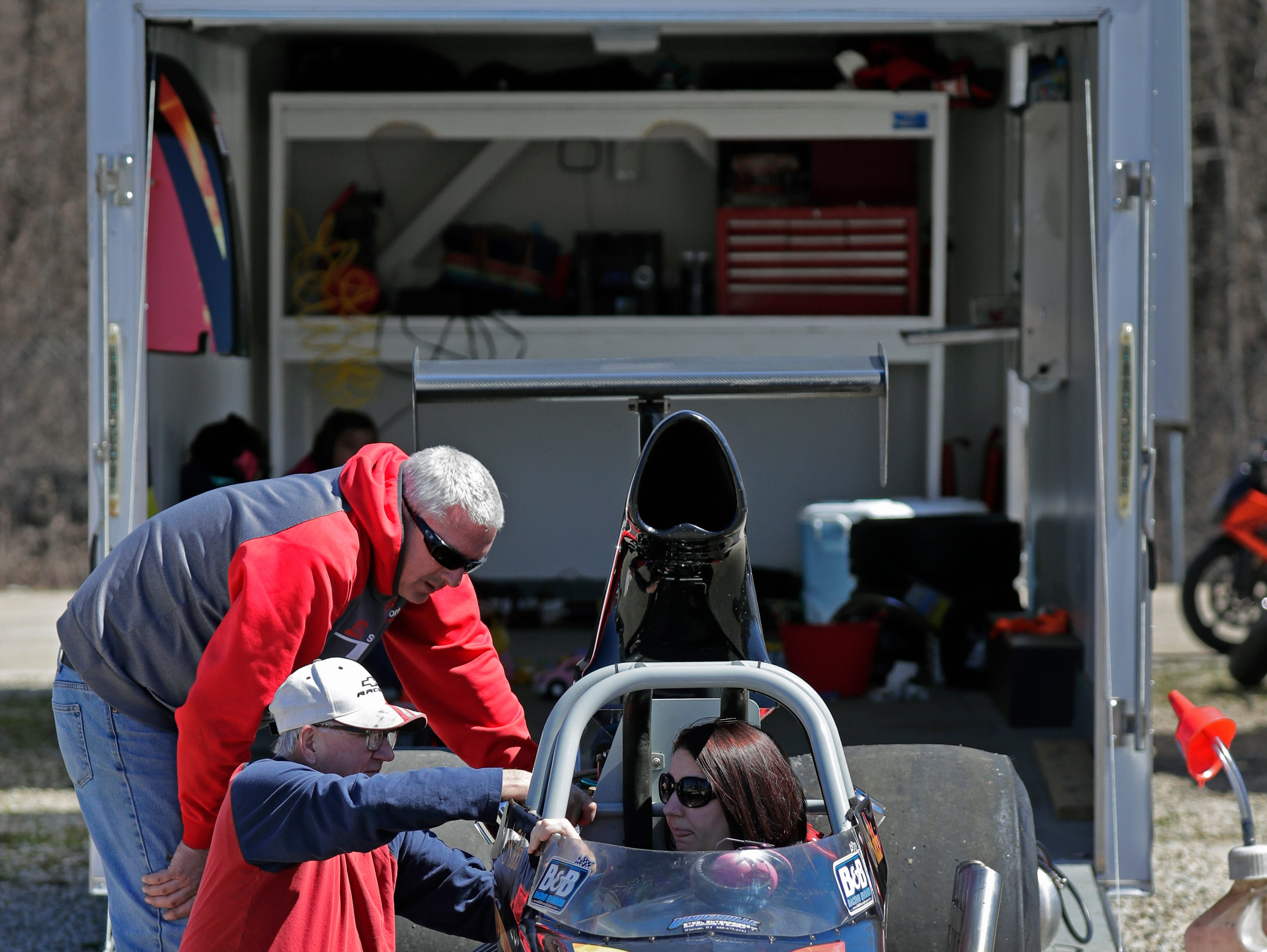 Steve Keller, left, of Appleton, Paul Londerville of Neenah and Nikki Keller, seated in car, make adjustments to their rear engine dragster during the Wisconsin International Raceway Strip Test & Tune event Saturday, April 20, 2019, in Kaukauna, Wis.