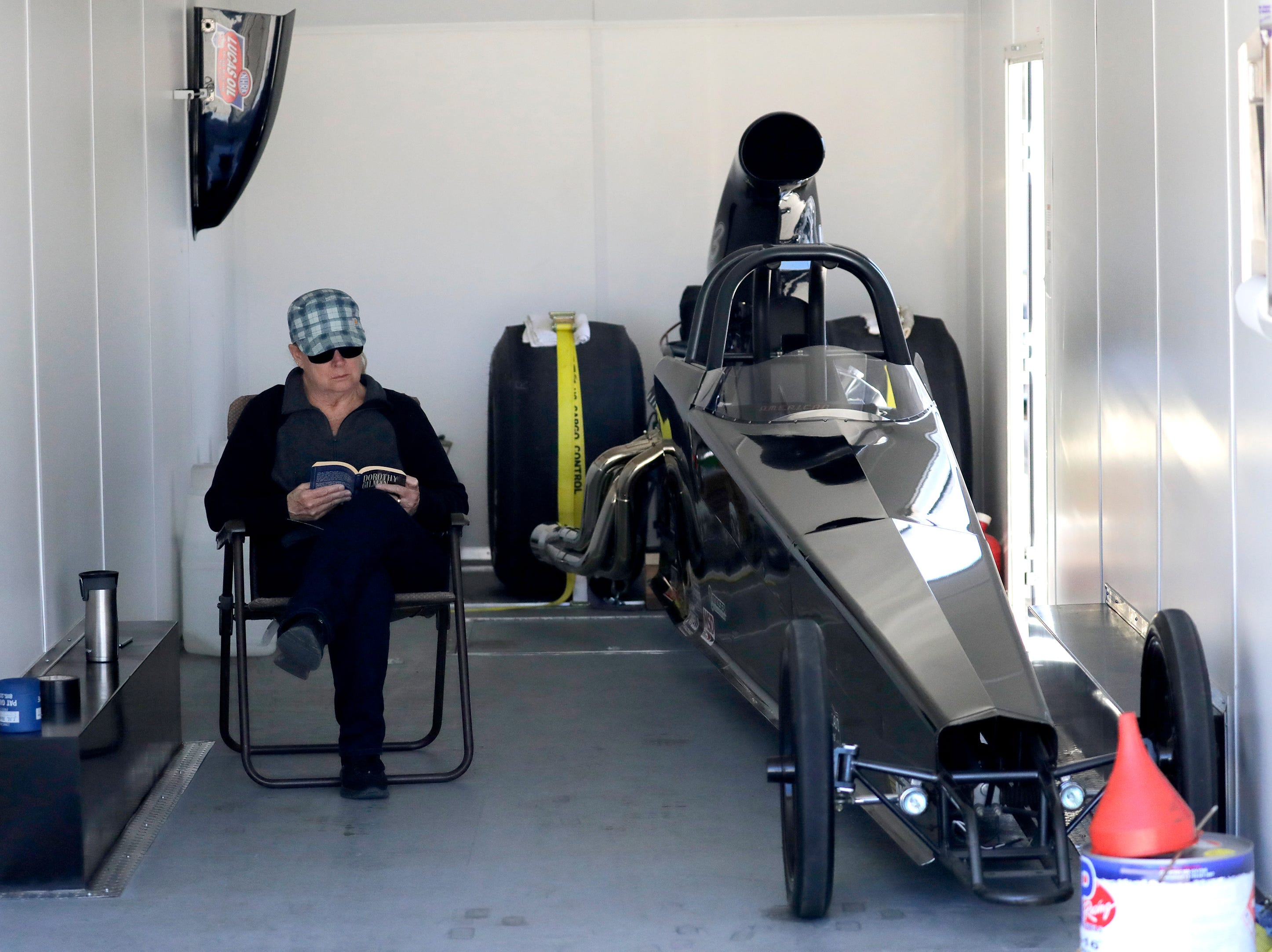 Mary Van Straten of De Pere reads a book inside her trailor while her husband works on a second dragster outside during the Wisconsin International Raceway Strip Test & Tune event Saturday, April 20, 2019, in Kaukauna, Wis. Drivers spent the day getting safety inspections, tune ups and test runs on the track for the upcoming season.