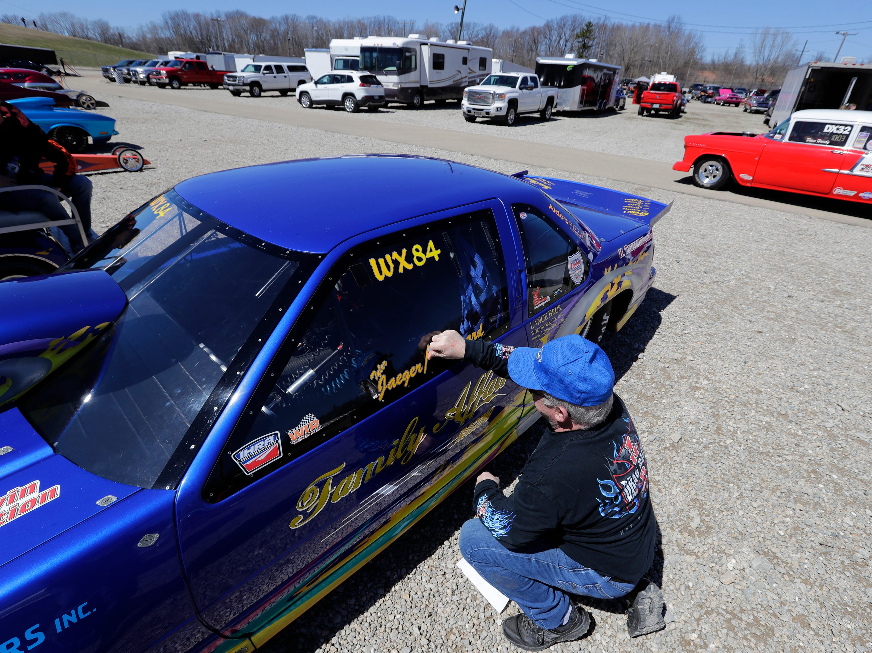 Myron Mertens of Green Bay puts decals on his dragster during the Wisconsin International Raceway Strip Test & Tune event Saturday, April 20, 2019, in Kaukauna, Wis. Drivers spent the day getting safety inspections, tune ups and test runs on the track for the upcoming season.