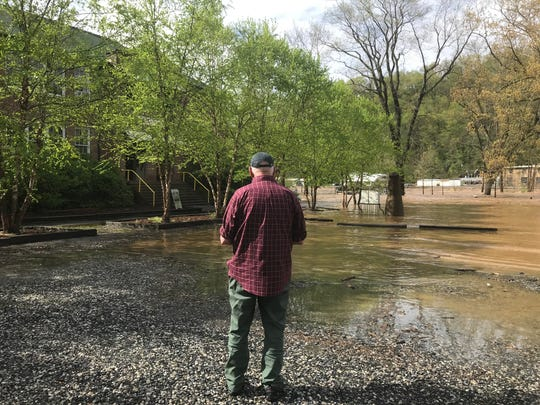 Rob Pulleyn stands outside Marshall High Studios April 19 as flood waters climb up Blannahassett Island in Marshall.