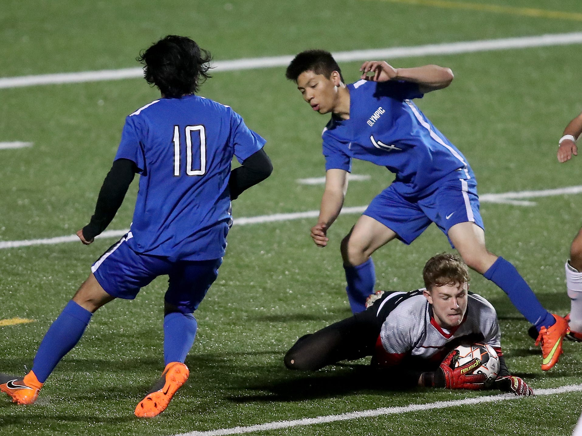 Port Townsend goalie Nico Winegar stops a shot by Olympic's Andrew Padilla (4) during the second half of their game at Silverdale Stadium on Friday, April 18, 2019.