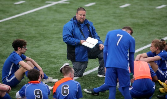 Olympic boys soccer coach Michael Wright addresses his team at halftime during the Trojans' game against Port Townsend on April 19, 2019.