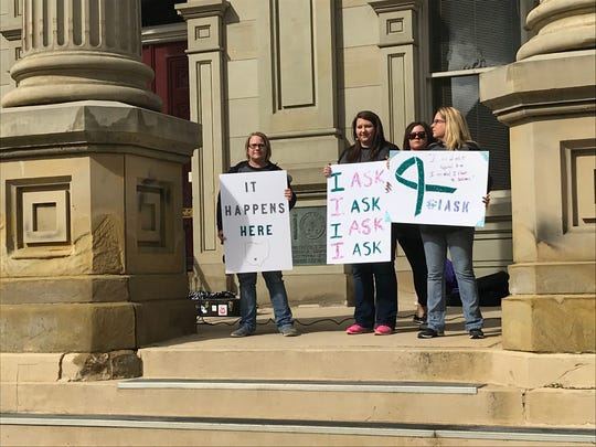 Survivor advocates hold up signs during speeches to raise awareness about sexual assault and interpersonal violence in Ross County. This year's theme is I Ask.