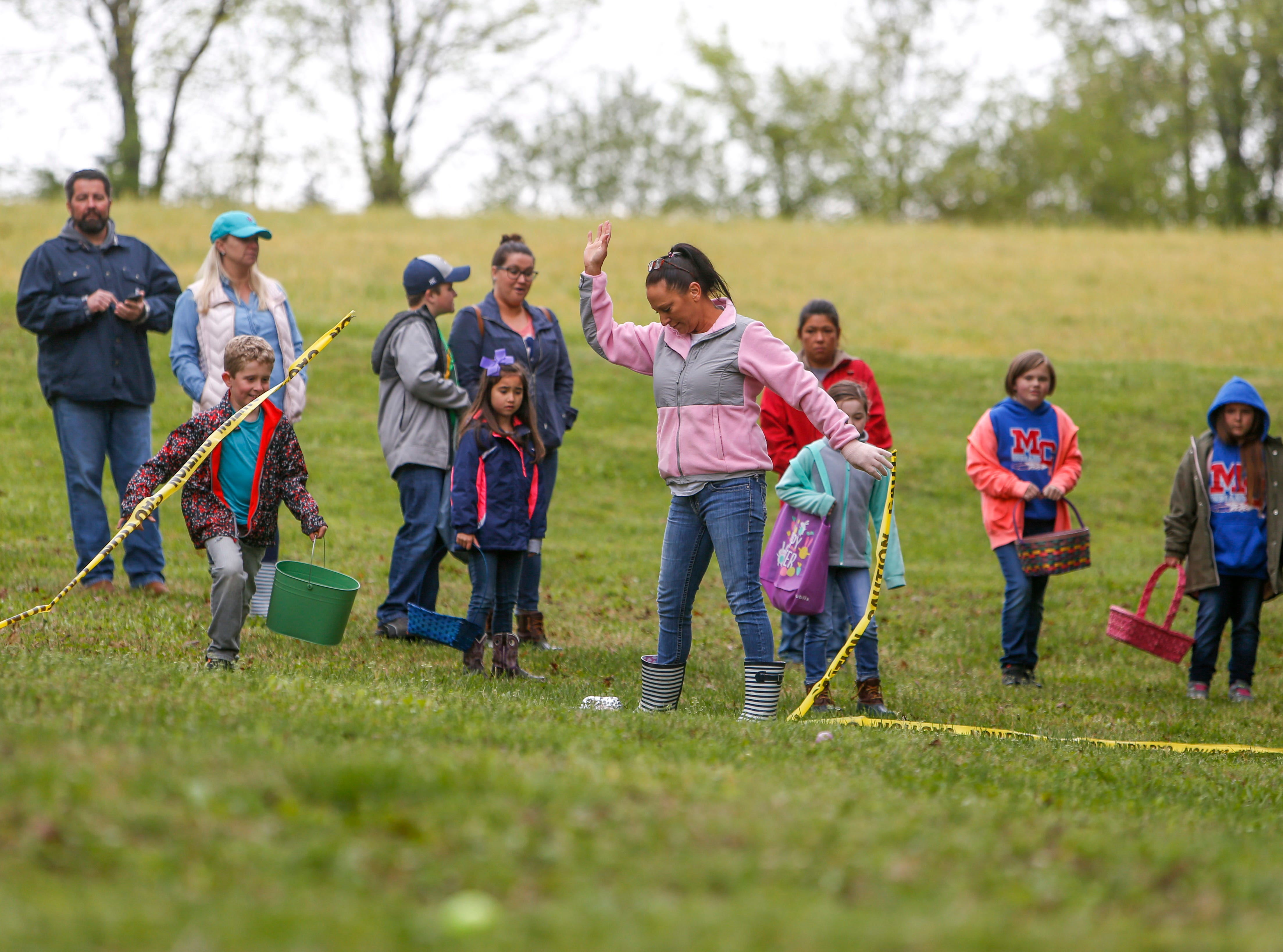 Linda Ebel snaps the barrier tape and lets egg hunters loose at the annual Easter egg hunts at Historic Collinsville in Clarksville, Tenn., on Saturday, April 20, 2019.