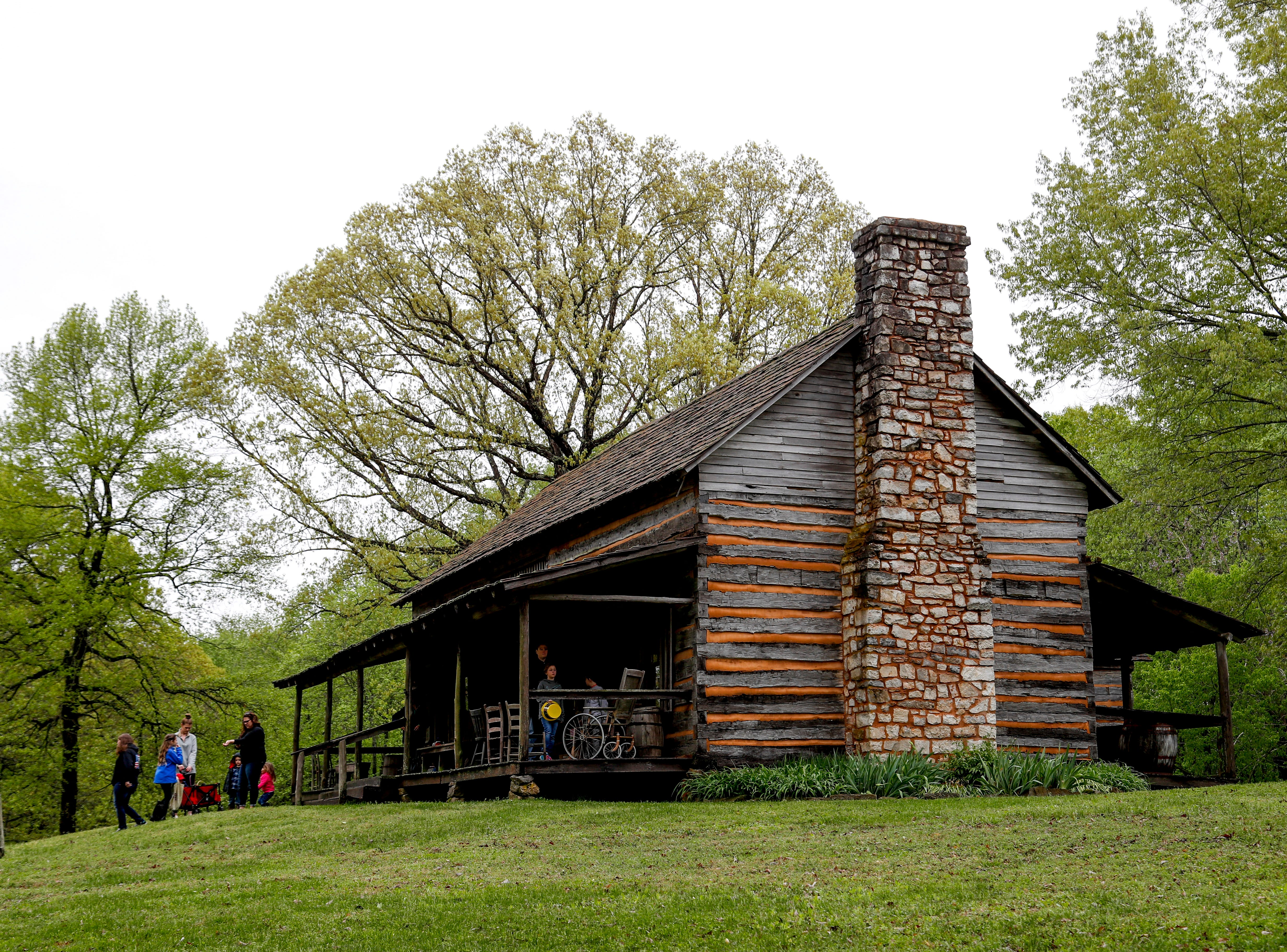 A family walks up the hills alongside an old preserved building at the annual Easter egg hunts at Historic Collinsville in Clarksville, Tenn., on Saturday, April 20, 2019.