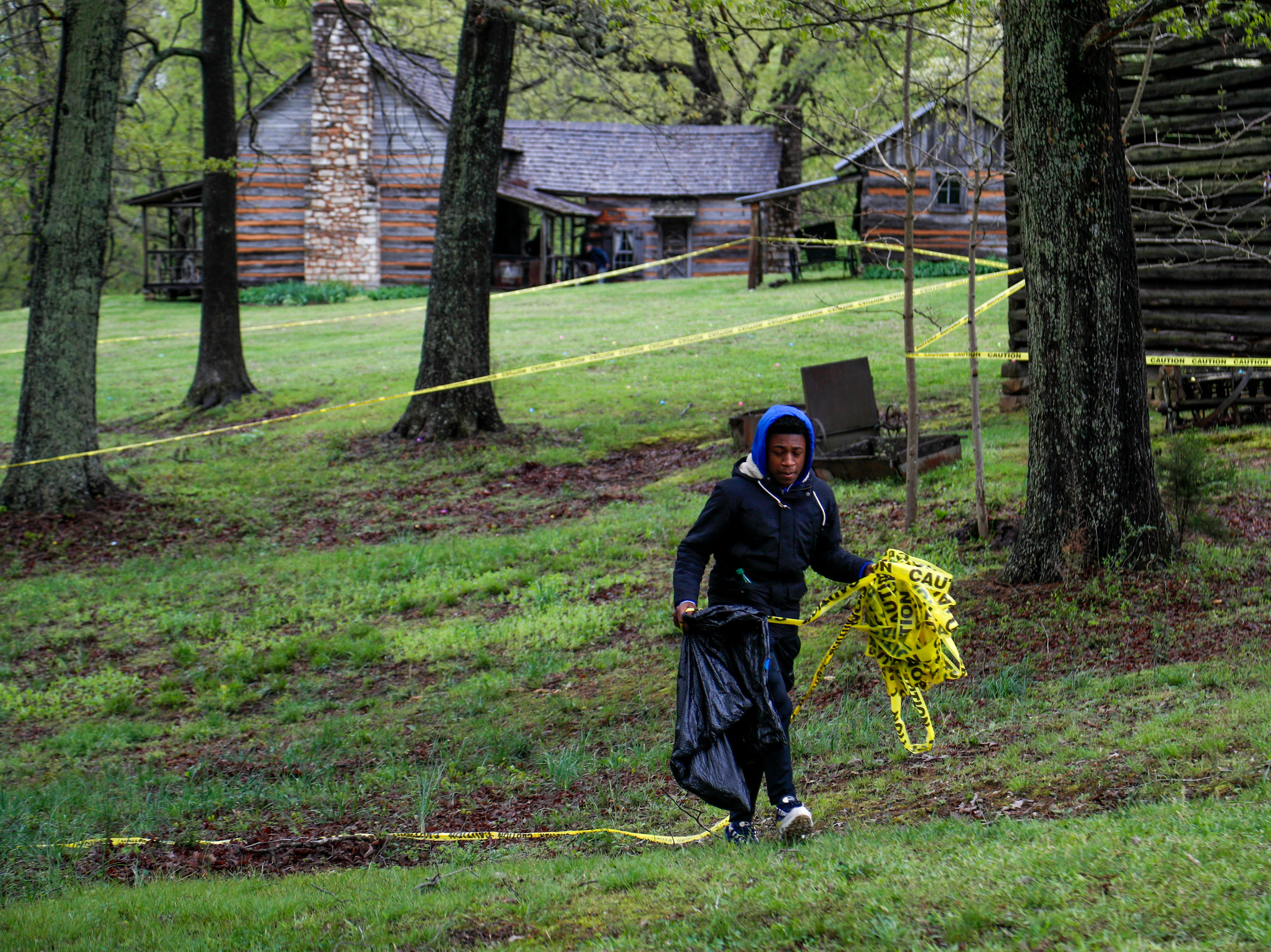 A volunteer removes barrier tape that was used to mark off egg hunts for different age groups at the annual Easter egg hunts at Historic Collinsville in Clarksville, Tenn., on Saturday, April 20, 2019.