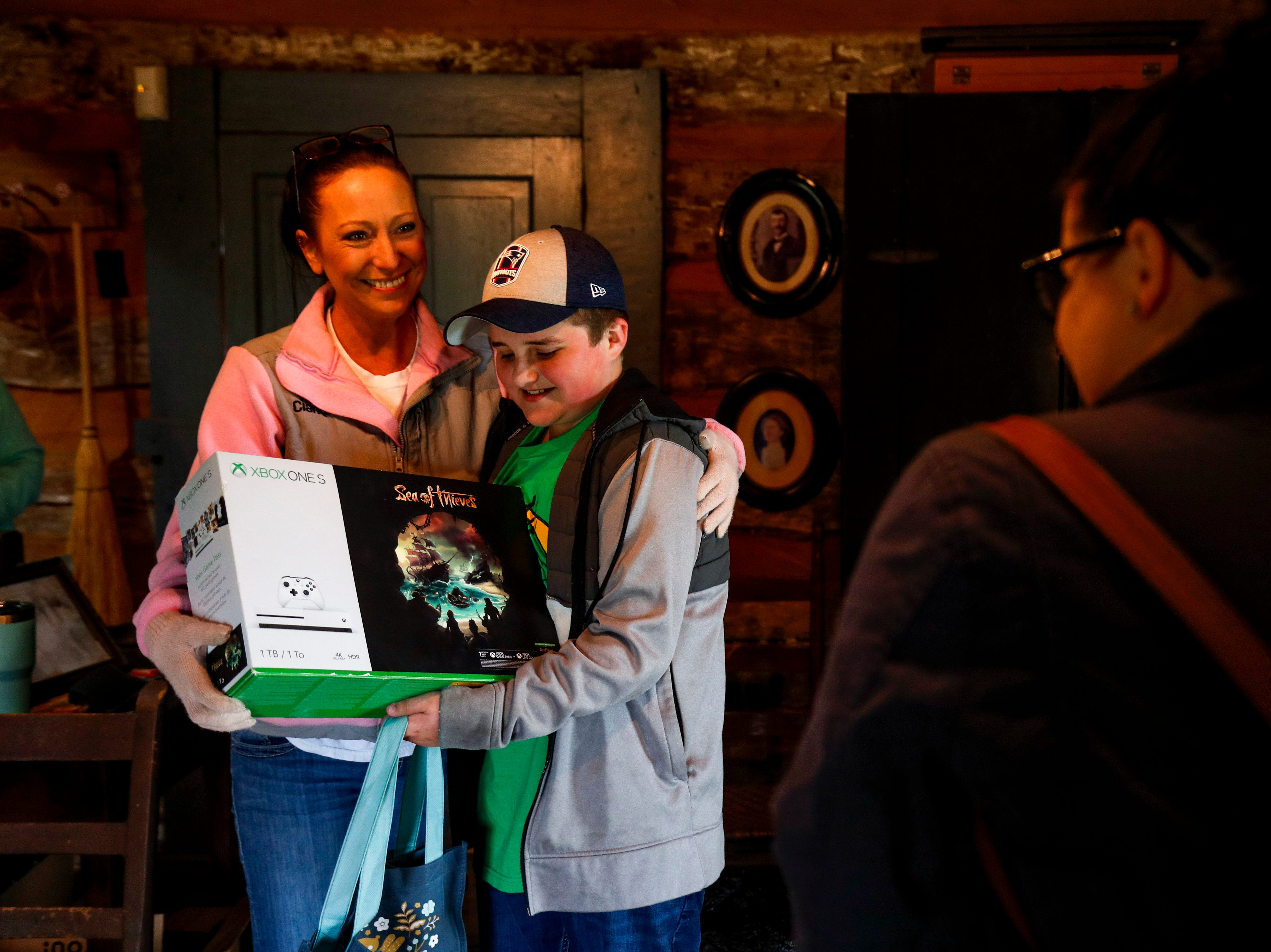 Jessica Workman, right, snaps a photo of her son Slate Workman, center, and Linda Ebel, left, with his prize for finding the golden egg at the annual Easter egg hunts at Historic Collinsville in Clarksville, Tenn., on Saturday, April 20, 2019.