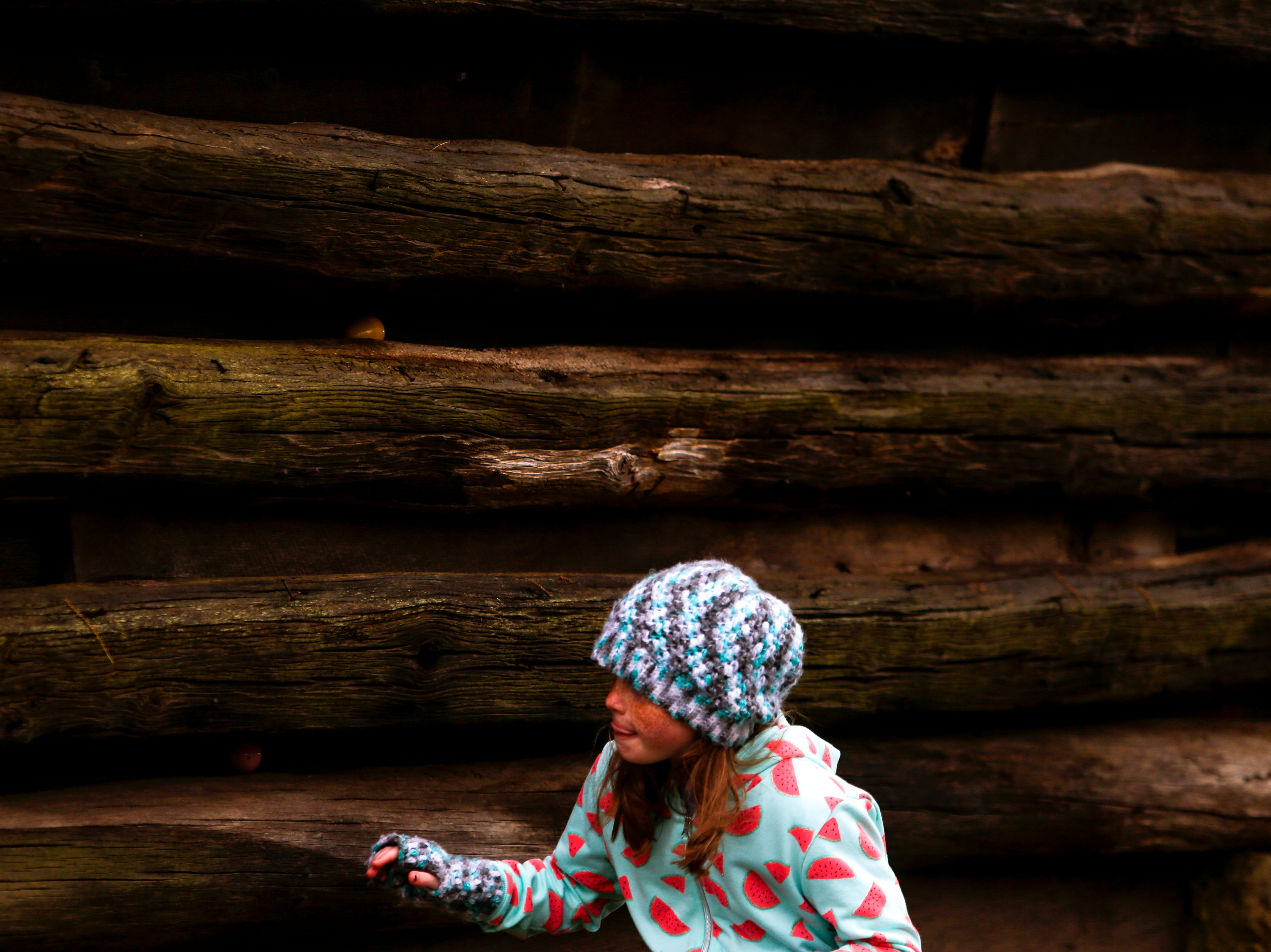 An egg hunter sneaks around the walls of a tobacco barn at the annual Easter egg hunts at Historic Collinsville in Clarksville, Tenn., on Saturday, April 20, 2019.