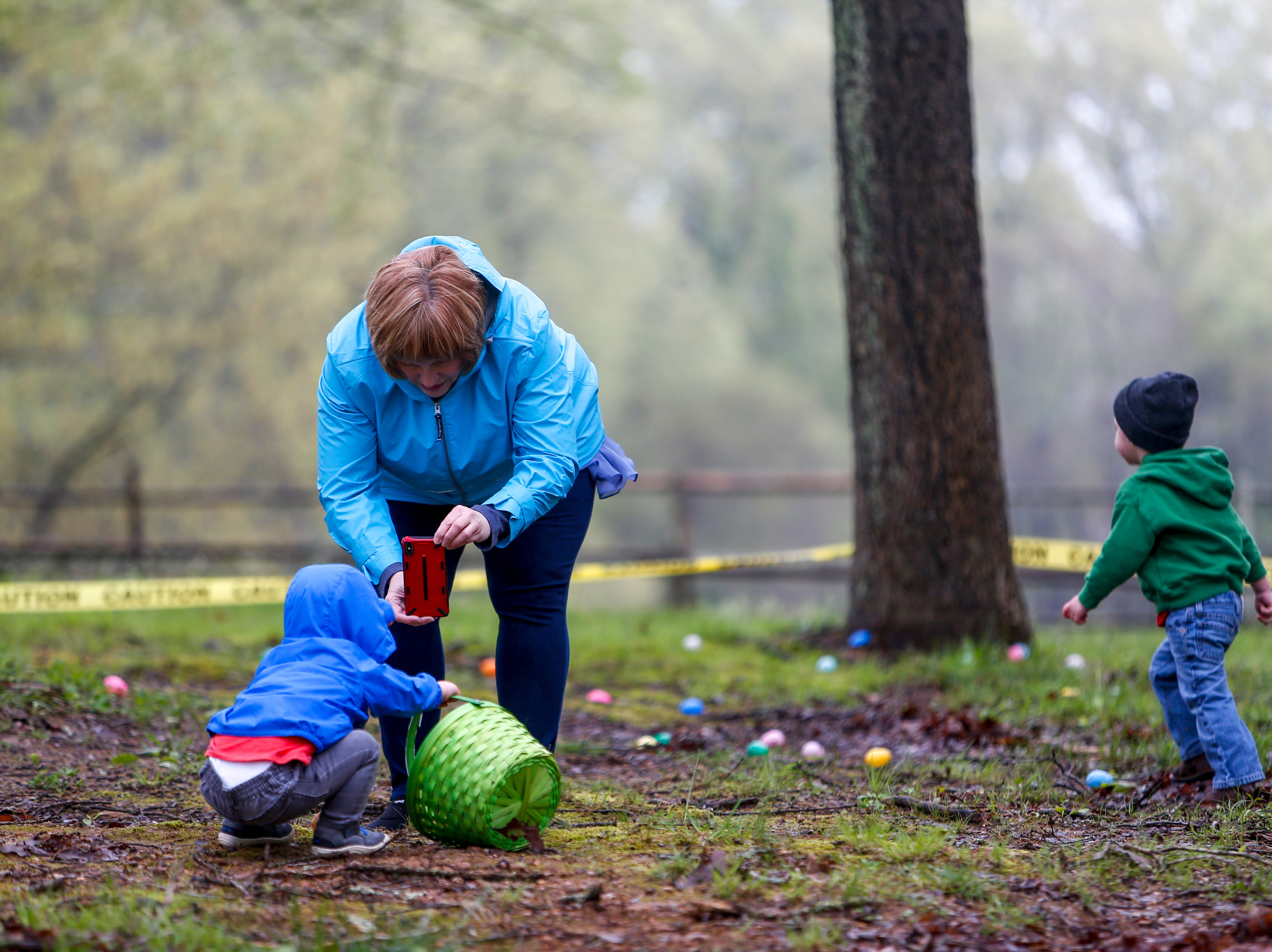Egg hunters run around in search of eggs and family snaps photos of them and their loot at the annual Easter egg hunts at Historic Collinsville in Clarksville, Tenn., on Saturday, April 20, 2019.