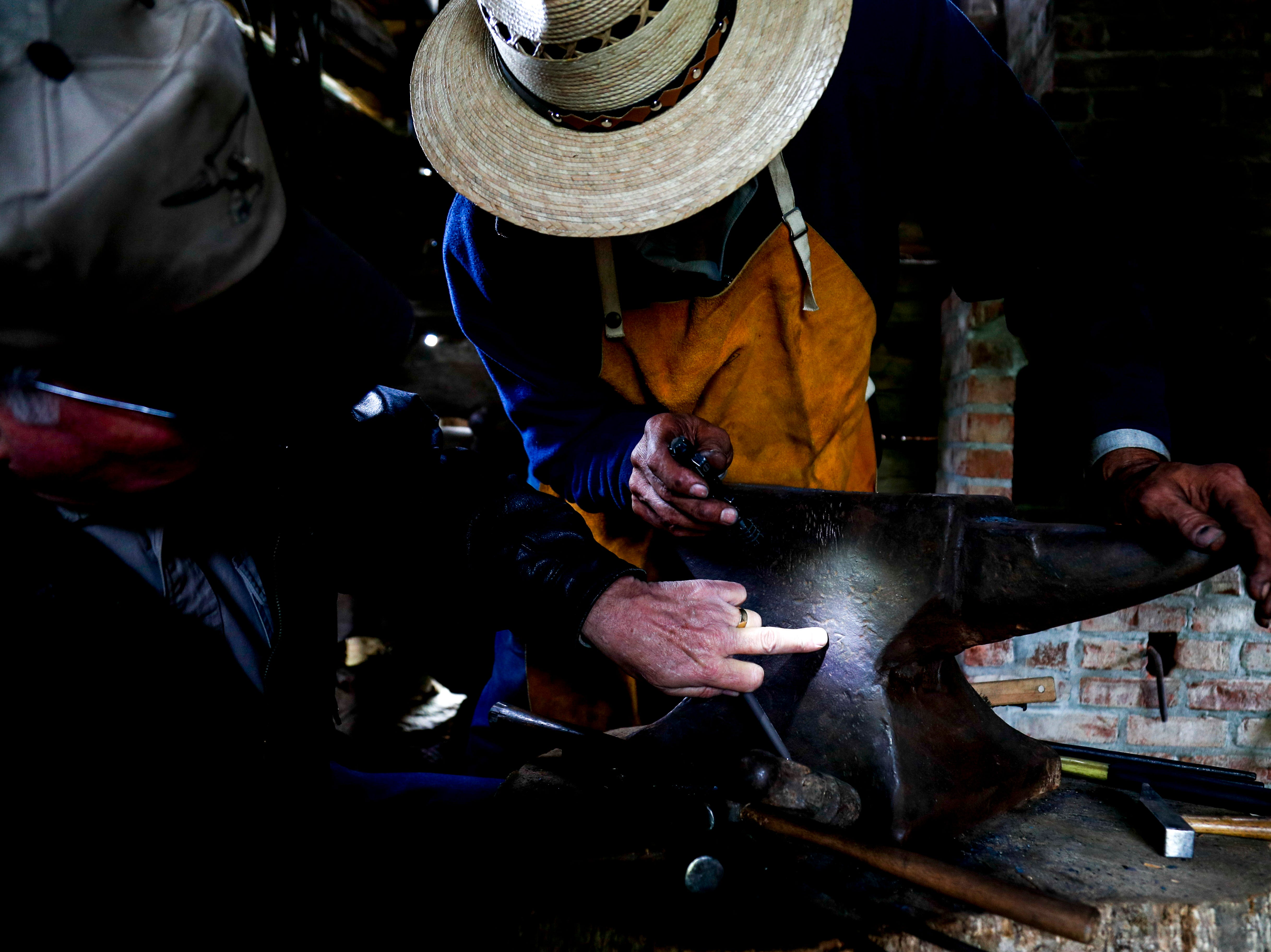 Ramiro Santoyo, center, and Larry Cole, left, examine an anvil inside the blacksmith shop to determine it's age at the annual Easter egg hunts at Historic Collinsville in Clarksville, Tenn., on Saturday, April 20, 2019.