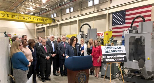 In this Thursday, April 18, 2019, photo, Gov. Gretchen Whitmer, center, helps unveil legislation that would offset tuition costs for students seeking a college degree or training certificate during a news conference at the Lansing Community College West Campus in Delta Township, Mich.