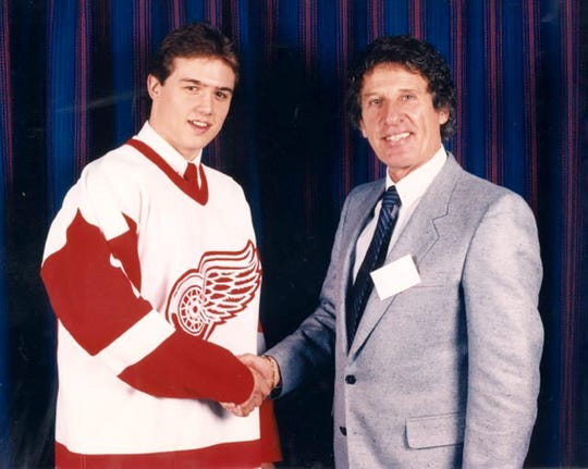 A young Steve Yzerman and Wings owner Mike Ilitch shake hands in a 1983 photo from Yzerman's rookie year with the Red Wings.