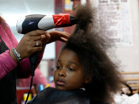Chyna Fenderson, 7 of Detroit waits patiently as hair stylist Nicora Lile works on the process of straightening and curling her hair at Little Willie's on Grand River Avenue in Detroit on Saturday, April 20, 2019.