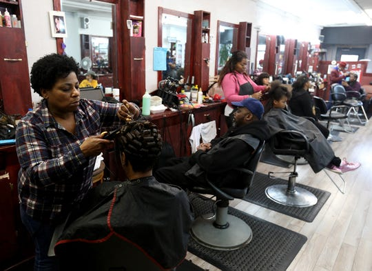 (left to right) Hair stylist Renee Hinton works on the hair of her client Sharon Johnson at Little Willie's on Grand River Avenue talks with her inside his hair salon in Detroit on Saturday, April 20, 2019.