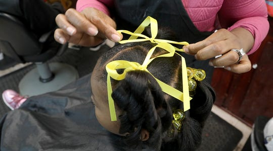Hair stylist Nicora Lile ties yellow ribbons into the hair of Chyna Fenderson, 7 of Detroit at Little Willie's on Grand River Avenue in Detroit on Saturday, April 20, 2019.