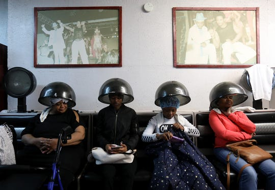 (left to right) Janice Thomas, TaCari Love, Kiara Cooper and Loreen Gordon all pass the time while getting their hair dried at Little Willie's on Grand River Avenue in Detroit on Saturday, April 20, 2019.