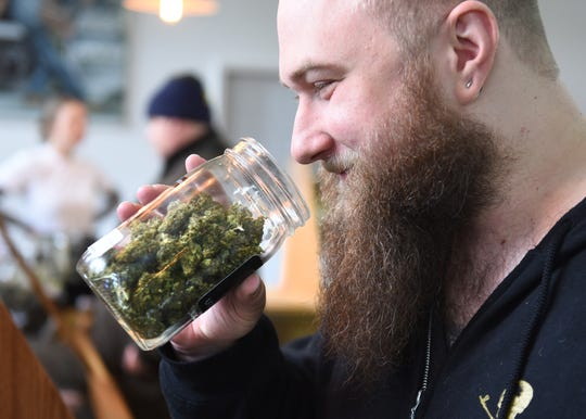 Matthew Carter of Madison Heights gets a nose full of Sour Diesel marijuana as the smells come from tiny molecules called terpenes during a 420 block party at Utopia Gardens in Detroit on April 20, 2019.