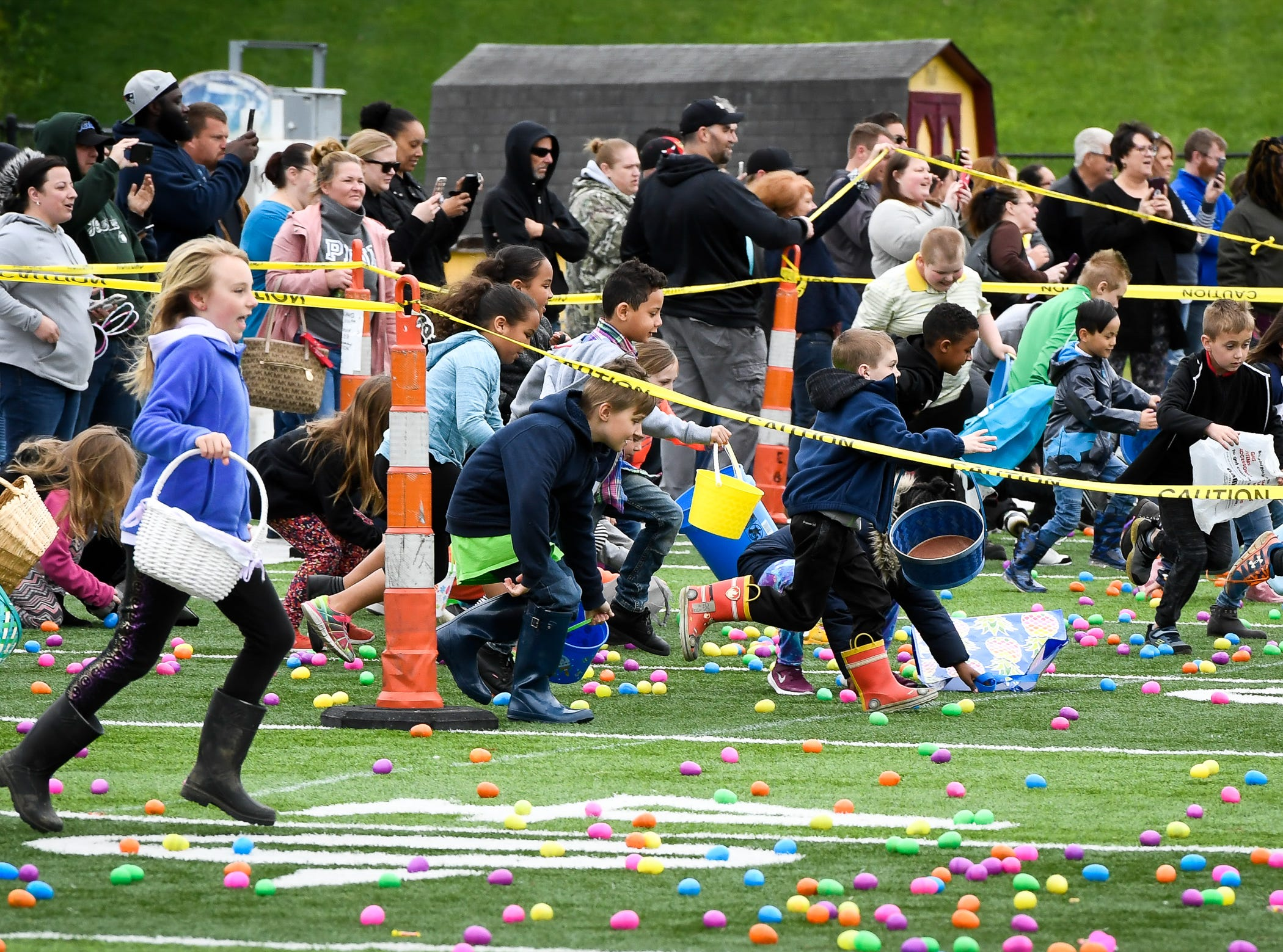 Kids rush to collect eggs at the 72nd annual West Side Nut Club Easter Egg Hunt Saturday, April 20, 2019.