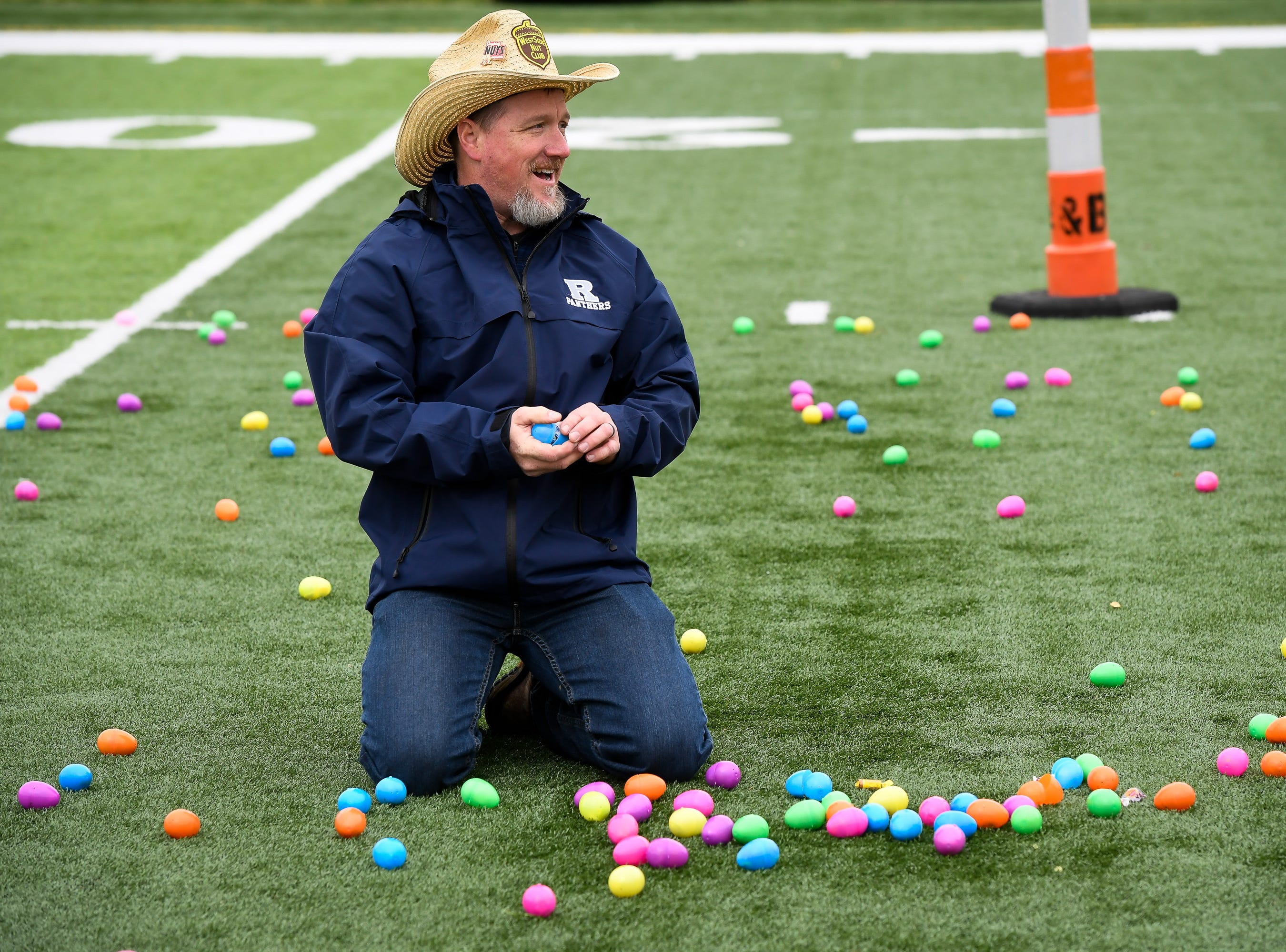 Chris Stewart spreads eggs out for the 72nd annual West Side Nut Club Easter Egg Hunt held at Mater Dei High Saturday, April 20, 2019.
