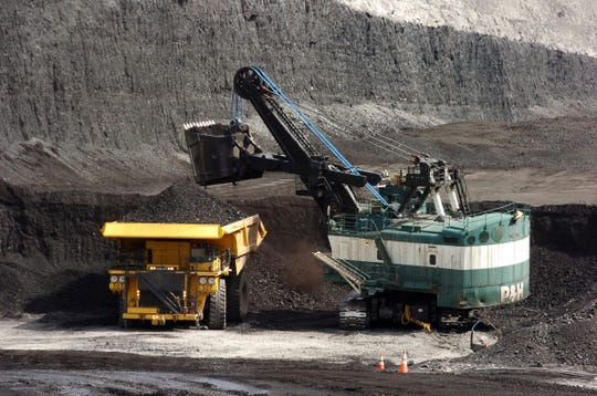 FILE - In this April 4, 2013, file photo, a mechanized shovel loads a haul truck with coal at the Spring Creek coal mine near Decker, Mont. A federal judge in Montana says the Trump administration failed to consider the environmental effects of resuming coal sales from federal lands, but stopped short of halting future sales. U.S. District Judge Brian Morris on Friday, April 19, 2019, ordered government attorneys to enter negotiations with states and environmental groups that had sued to stop the lease sales. (AP Photo/Matthew Brown, File)