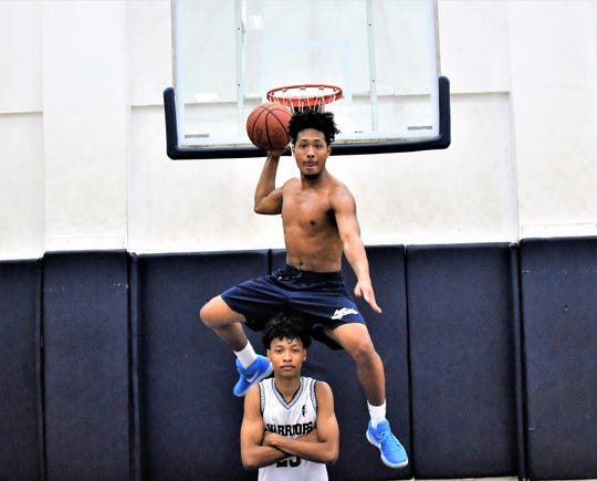 Morgan Aiken IV, top, leaps over his younger brother Reo Aiken. Reo hopes to play pro basketball one day. Morgan Aiken IV played pro basketball in Japan for two years.