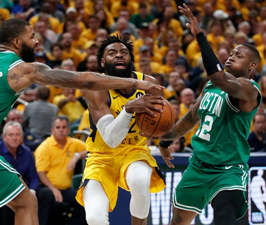 Indiana Pacers guard Tyreke Evans (12) drove between Boston Celtics forward Marcus Morris (13) and Terry Rozier (12) in the second half of their game at Bankers Life Fieldhouse on Friday.