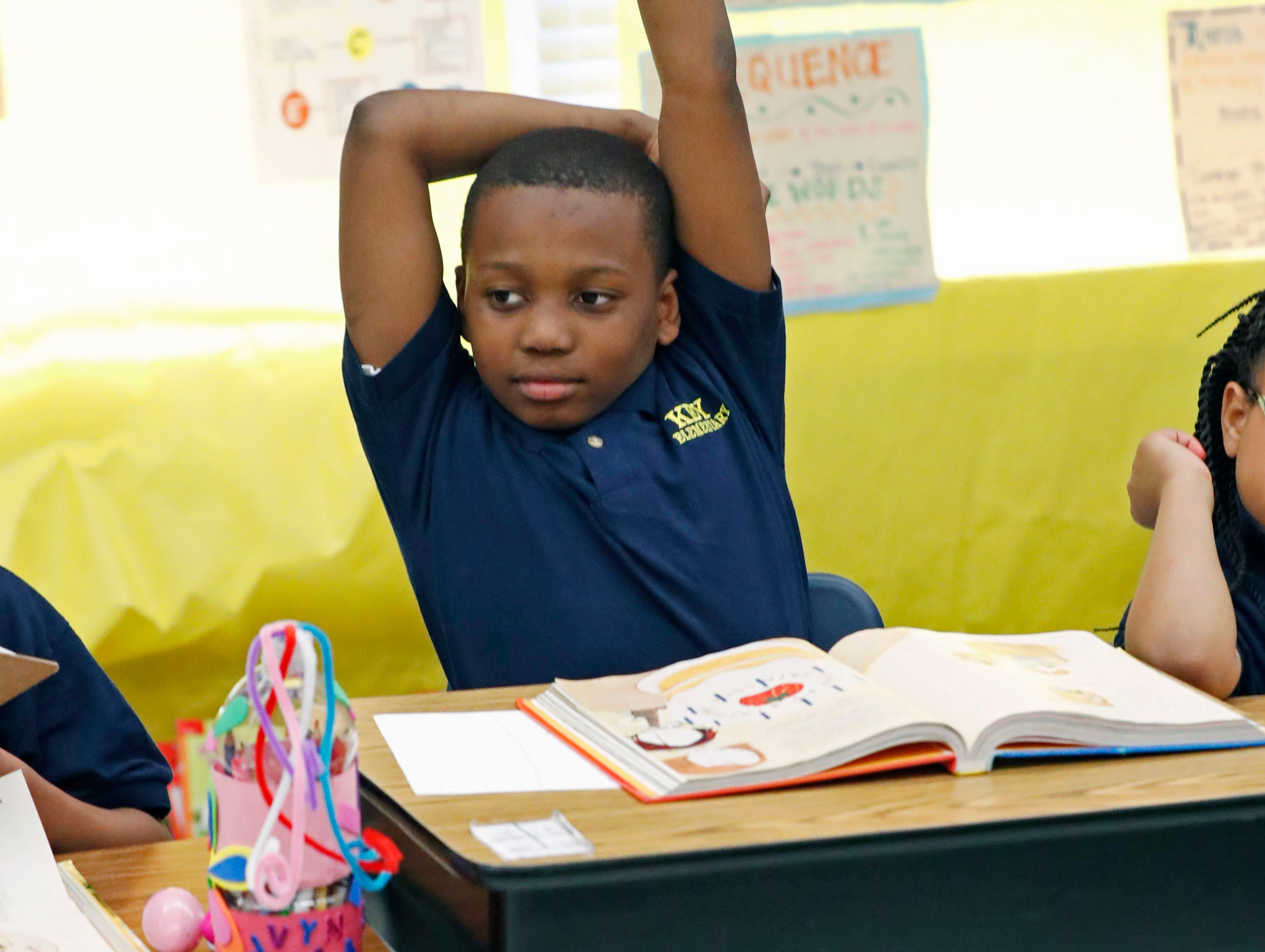"""Anthony Wilder, a Key Elementary School third grade student, raises his arm with a reading question answer Thursday, April 18, 2019, in Jackson, Miss. More than 35,000 Mississippi third graders sat down in front of computers this week to take reading tests, facing a state mandate to """"level up"""" or not advance to fourth grade. And with the bar set higher this year, state and local officials expect more students will fail the initial test, even with efforts to improve teaching. (AP Photo/Rogelio V. Solis)"""