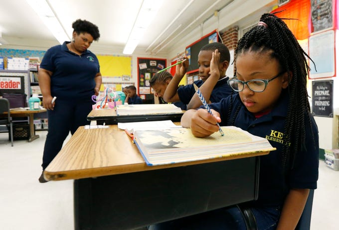 """Elize'a Scott, a Key Elementary School third grade student, right, reads under the watchful eyes of teacher Crystal McKinnis, left, Thursday, April 18, 2019, in Jackson, Miss. More than 35,000 Mississippi third graders sat down in front of computers this week to take reading tests, facing a state mandate to """"level up"""" or not advance to fourth grade. And with the bar set higher this year, state and local officials expect more students will fail the initial test, even with efforts to improve teaching. (AP Photo/Rogelio V. Solis)"""