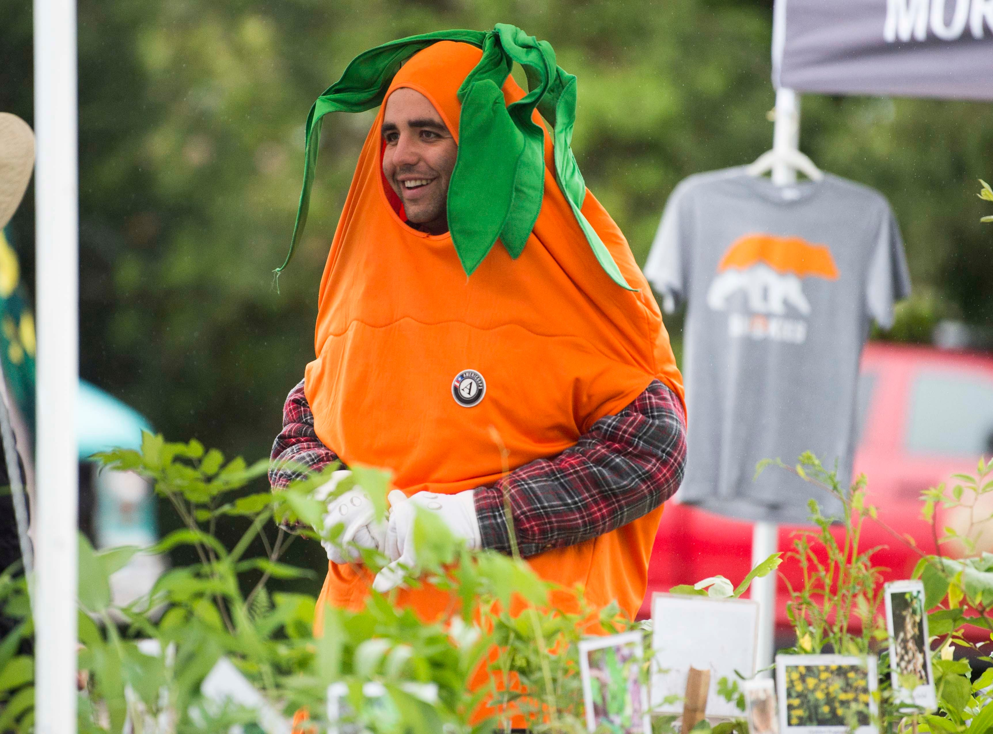 Dressed as a carrot, Justin Beach, of Knoxville, learns about the Native Plant Rescue Squad at Earthfest 2019 at the Knoxville Botanical Gardens in East Knoxville, Saturday, April 20, 2019.