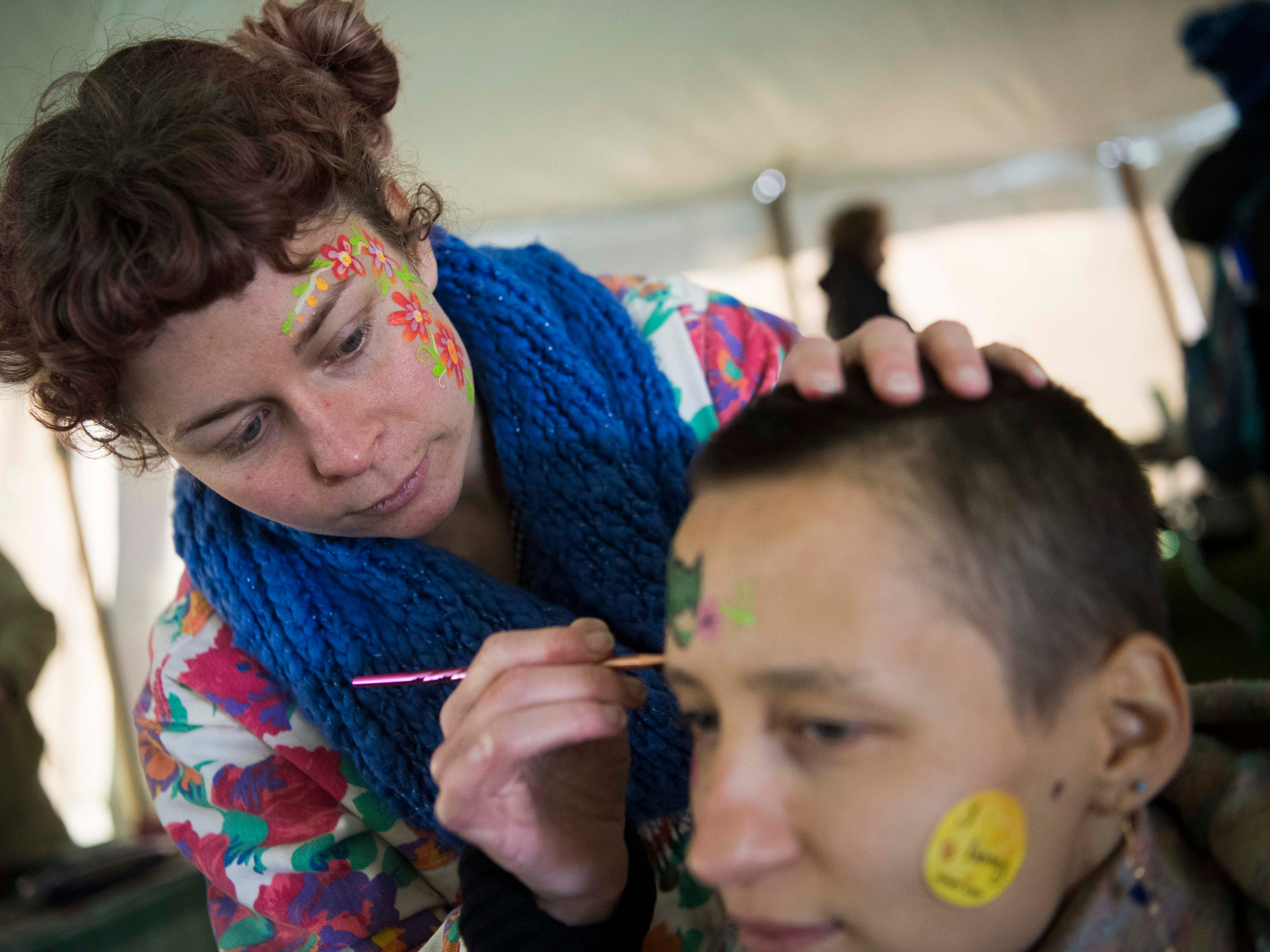 Emma McNall of Corelli art studio, paints Maria Campbell of West Knoxville's face at Earthfest 2019 at the Knoxville Botanical Gardens in East Knoxville, Saturday, April 20, 2019.