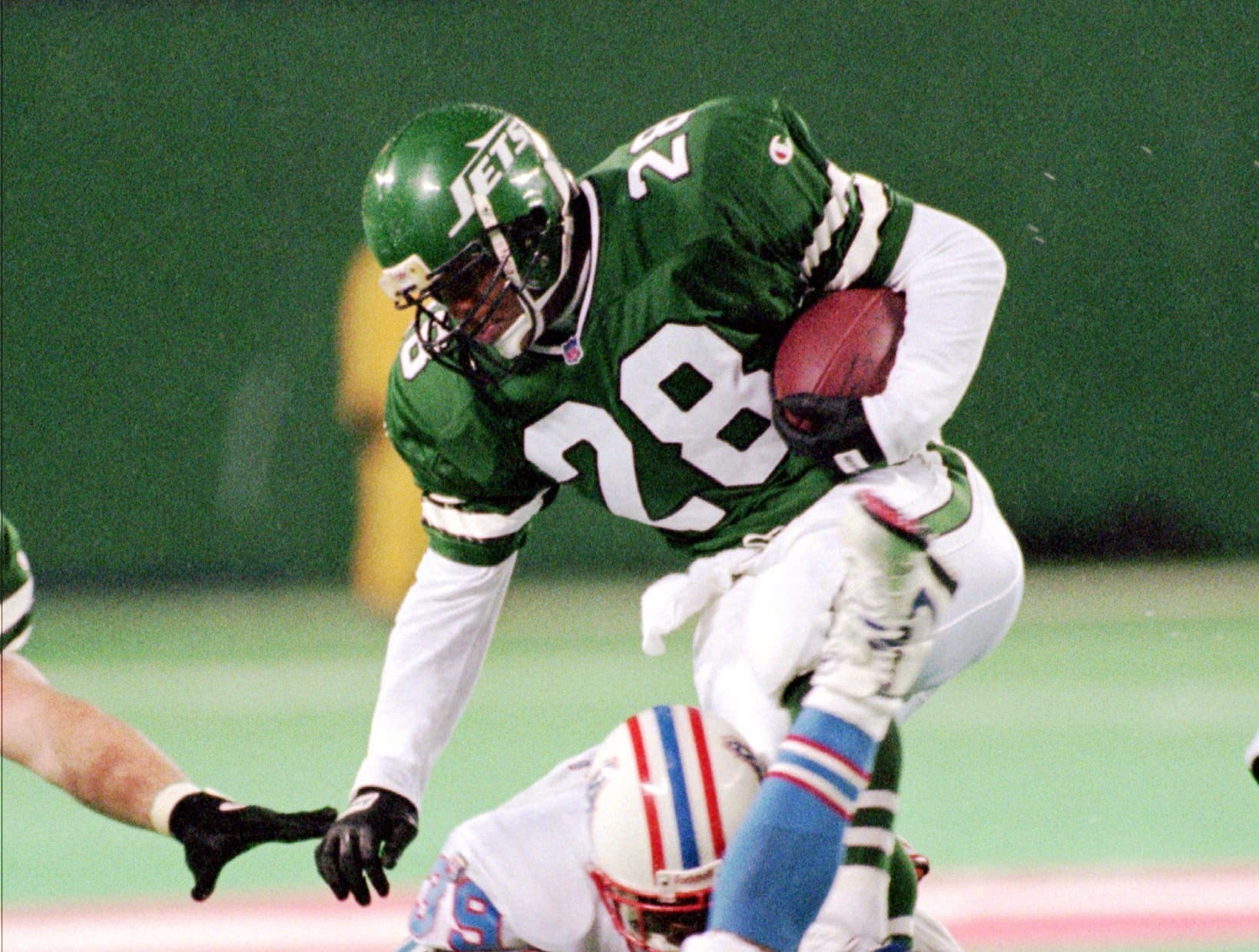 New York Jets kick returner Reggie Cobb (28) is tackled by Houston Oilers' Lee Cole (39) with help from teammate Rodney Thomas (20) after gaining 18 yards during the fourth quarter Sunday, Dec. 1, 1996, at Giants Stadium in East Rutherford, N.J. The Oilers beat the Jets 35-10.