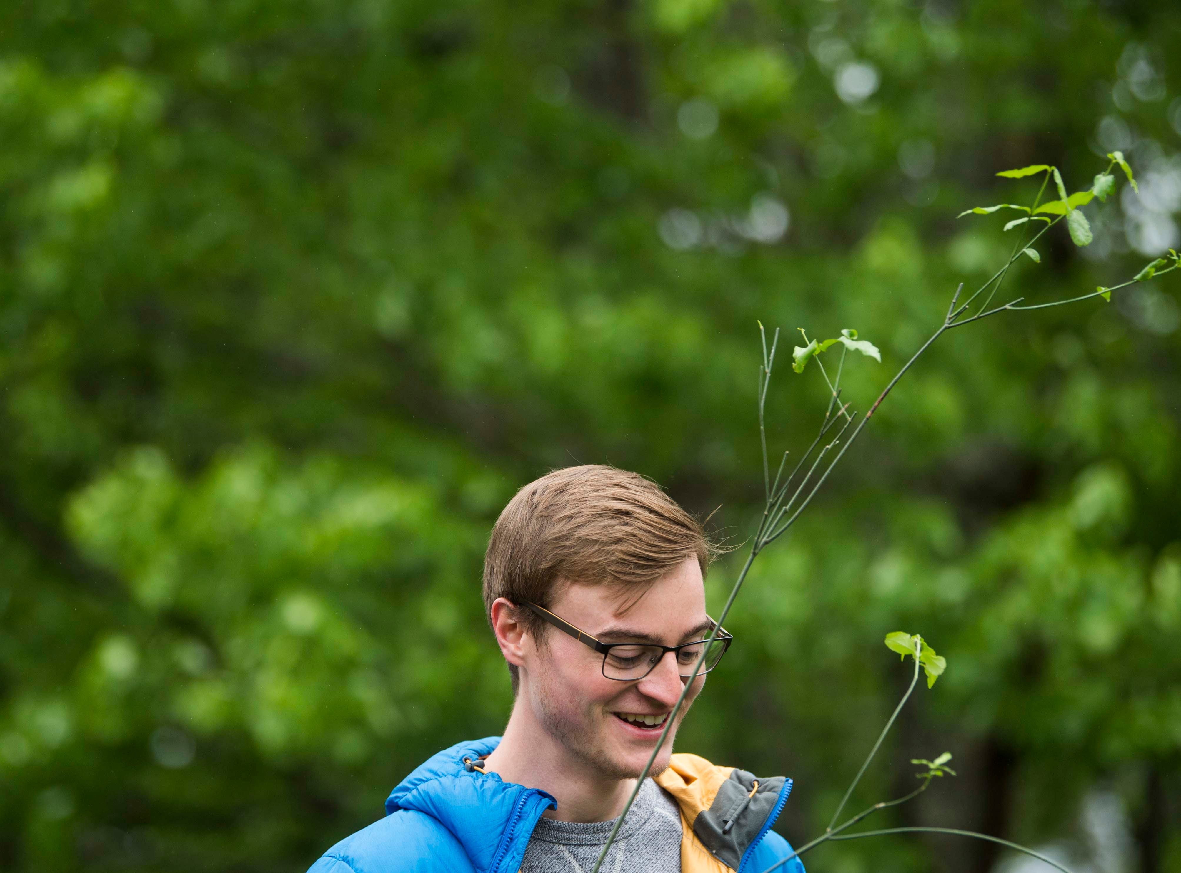 UT grad student Jonathan Cox, of Knoxville, holds onto a plant at Earthfest 2019 at the Knoxville Botanical Gardens in East Knoxville, Saturday, April 20, 2019.