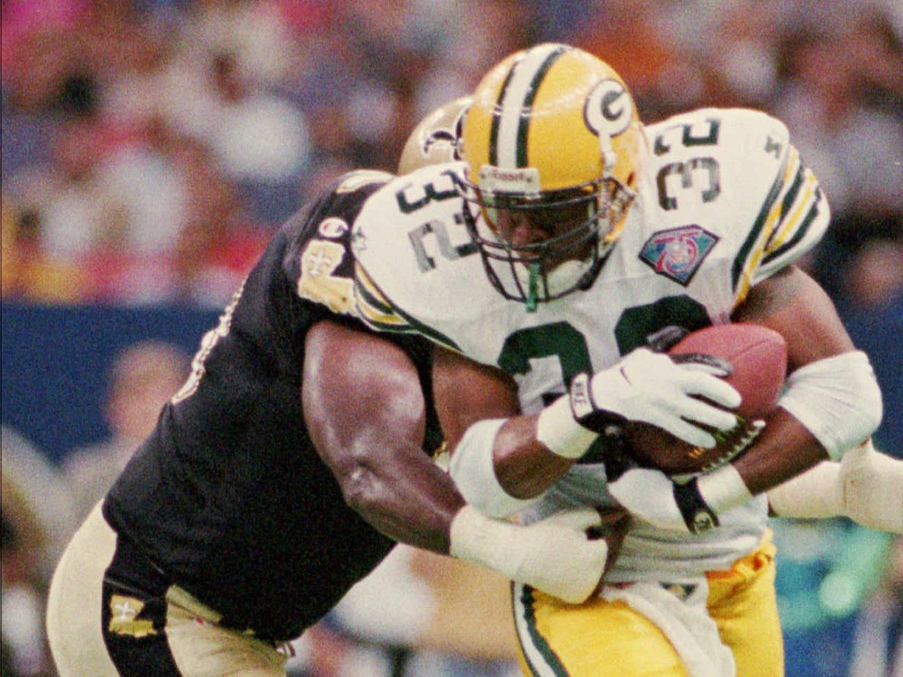 Green Bay Packers running back Reggie Cobb (32) tries to elude New Orleans Saints defender Frank Warren (73) during the first half Friday night, Aug. 19, 1994, in New Orleans. Cobb spun away from Warren and had a short gain on the play.