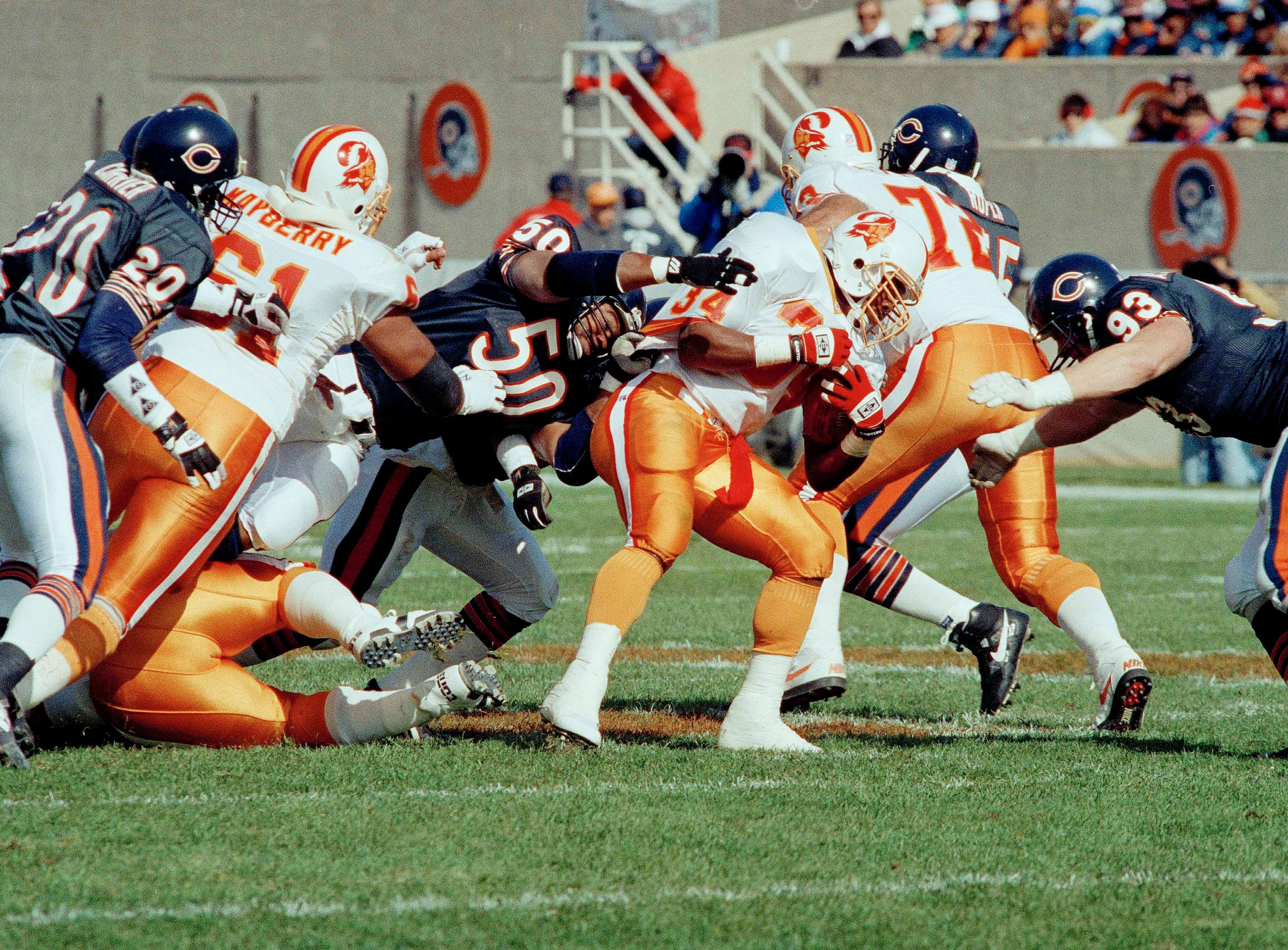 Tampa Bay Buccaneers running back Reggie Cobb (34) is stopped on a 7-yard run by Chicago Bears Mike Singletary (50) and Trace Armstrong (93) in the second quarter at Chicago's Soldier Field, Oct. 18, 1992.